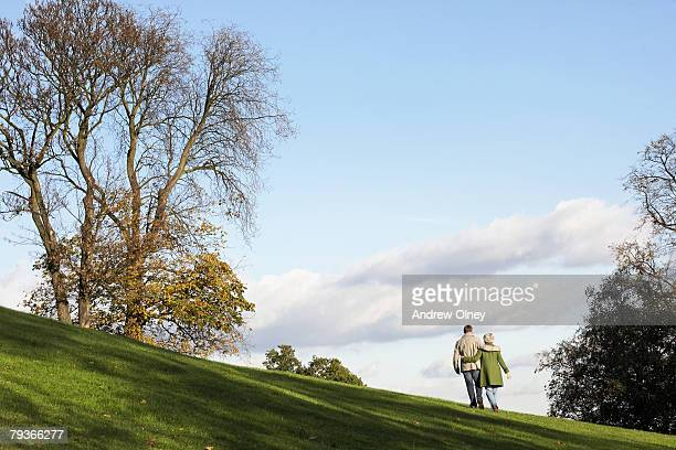 couple outdoors walking on a hillside - entfernt stock-fotos und bilder