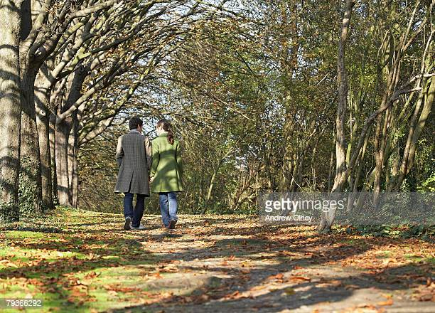 couple outdoors walking on a path in a park - 中年カップル ストックフォトと画像