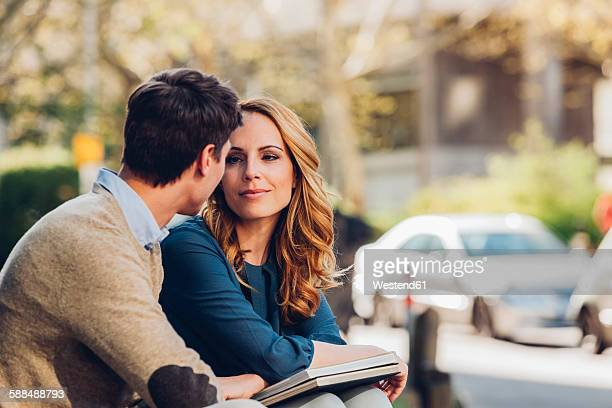 couple outdoors with book looking at each other - older woman younger man stock photos and pictures