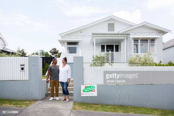 Couple outside house with sold sign