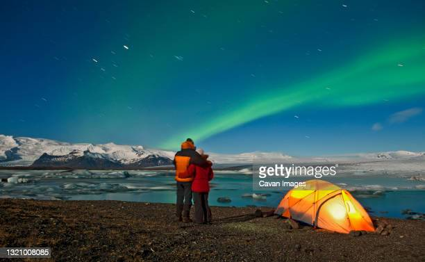 couple outside of their tent looking at northern lights in the sky - iceland stock pictures, royalty-free photos & images