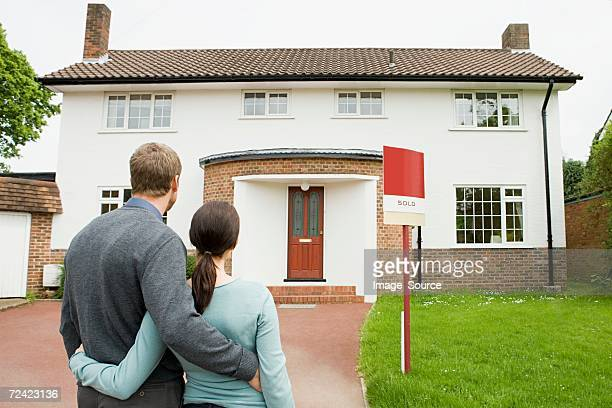 Couple outside their new house