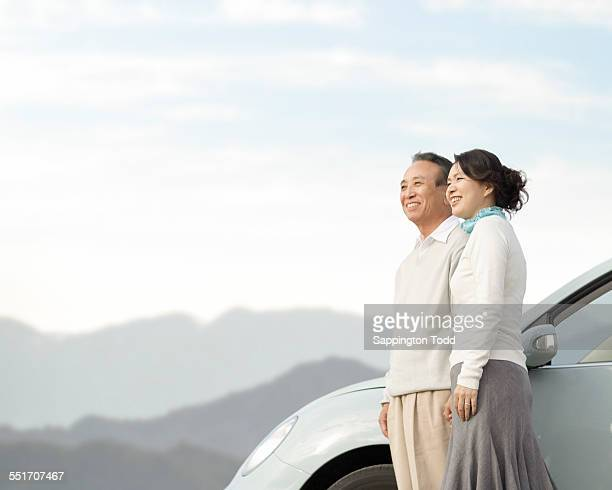 couple overlooking the distant standing near the car - 夫婦 ストックフォトと画像