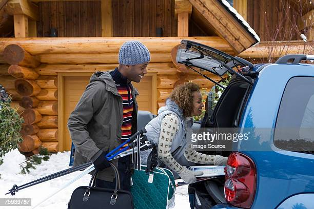 couple packing car boot - ski holiday stock photos and pictures