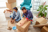 Couple packing things into cardboard boxes