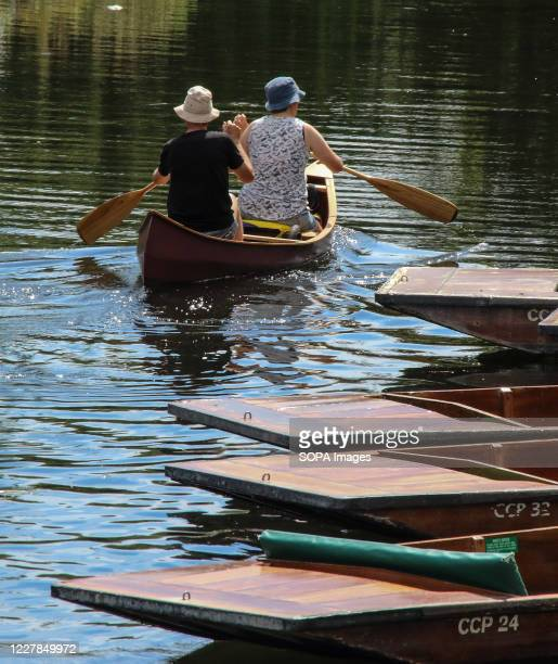 Couple paddle past some punts on a warm summer day. People relax during the warm summer weather as the temperature in England is expected to reach 30...