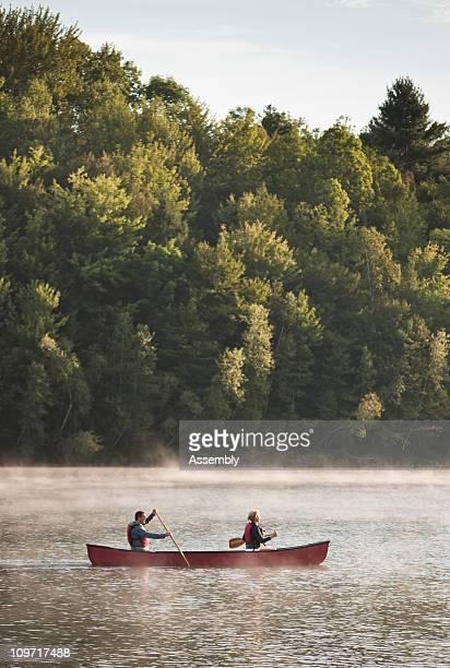 couple paddles a canoe at sunrise on a lake