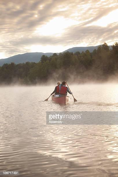 couple paddling canoe at sunrise on calm lake - paddling stock pictures, royalty-free photos & images