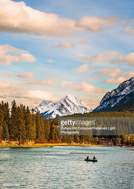 Couple paddling canoe on Bow River in Banff National Park with a snow-capped Mt. Rundle, Banff, Alberta, Canada