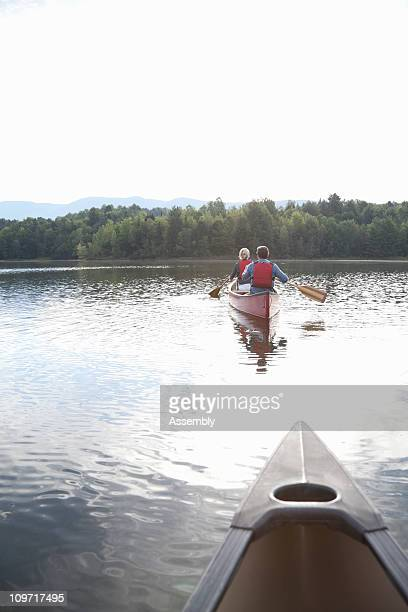 Couple paddling canoe on calm lake