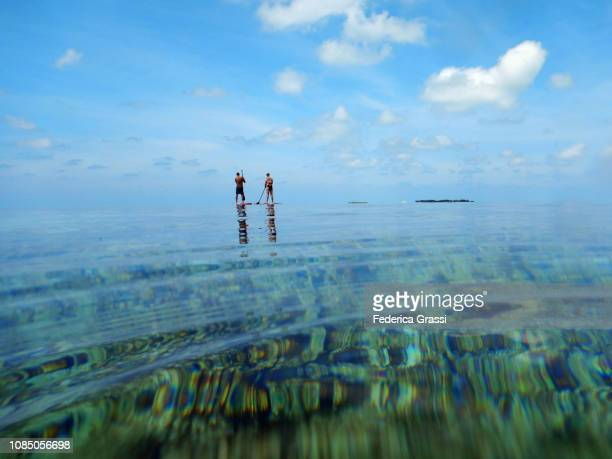 couple paddling in maldivian lagoon of eriyadu island - lagoon stock pictures, royalty-free photos & images