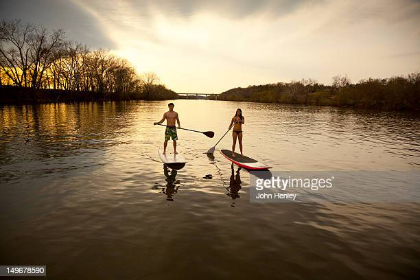 Couple paddling in river on surfboards