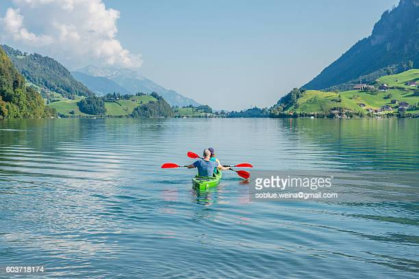A couple paddling on Lungernsee lake Lungern in Switzerland between the mountains alps landscape on a summer day