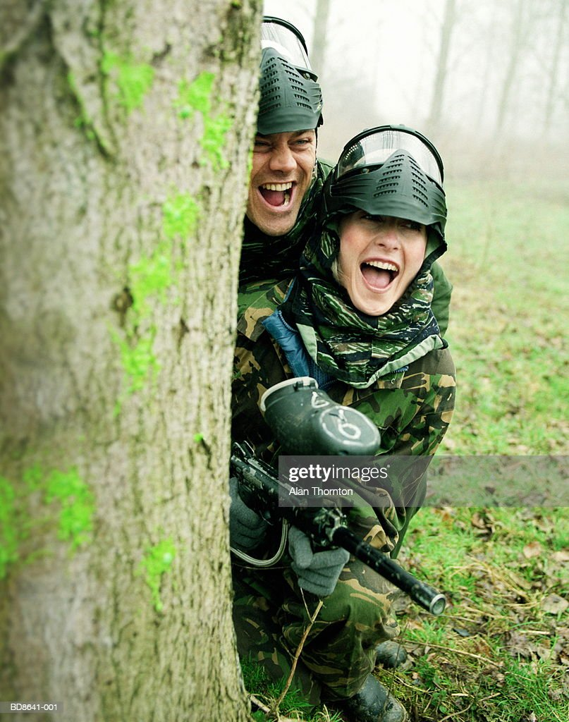 Couple paintballing, hiding behind tree : Stock Photo