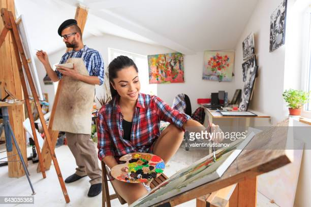 Couple painters drawing in art studio