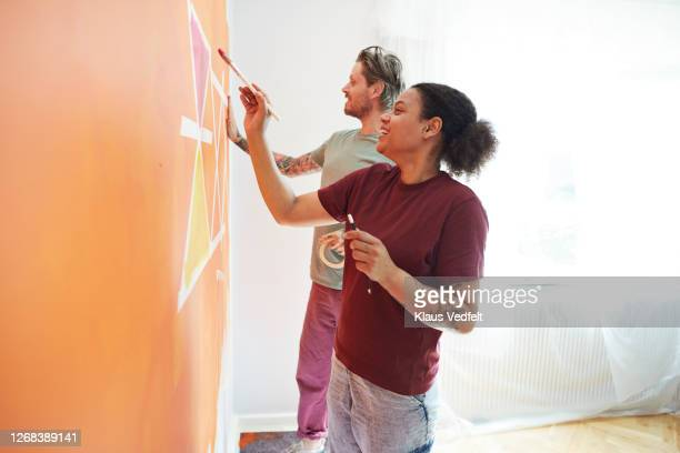 couple painting design on orange wall at home - lifestyle stock pictures, royalty-free photos & images