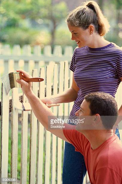 couple painting picket fence - staccionata foto e immagini stock