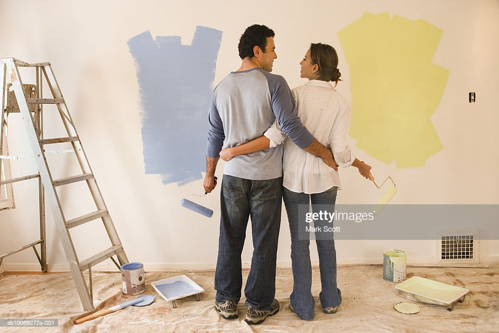 Couple painting room, rear view : Stockfoto