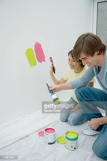 Couple Painting Together In New Home Stock Photo