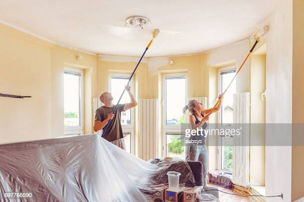 Couple painting wall and ceiling with telescopic roller