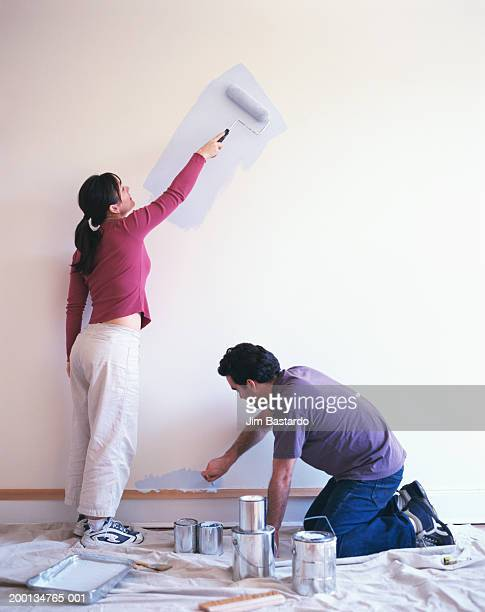 Couple painting wall, side view