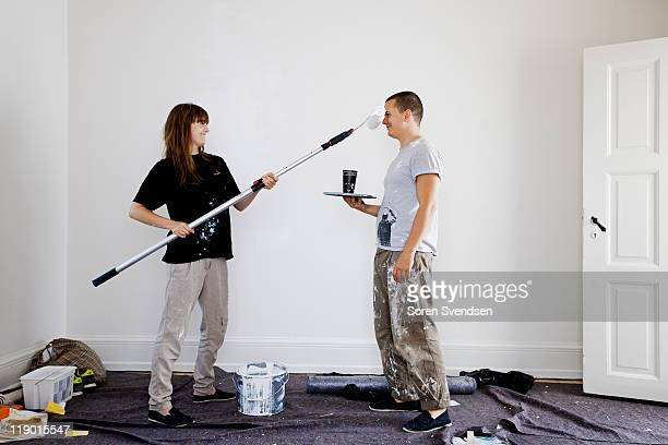 couple painting walls of new home - bricolage humour photos et images de collection