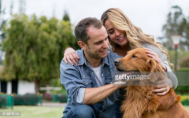 Couple pampering a beautiful dog