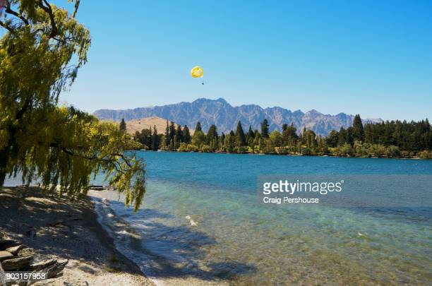 Couple parasailing above high Queenstown Bay and The Remarkables mountain range.