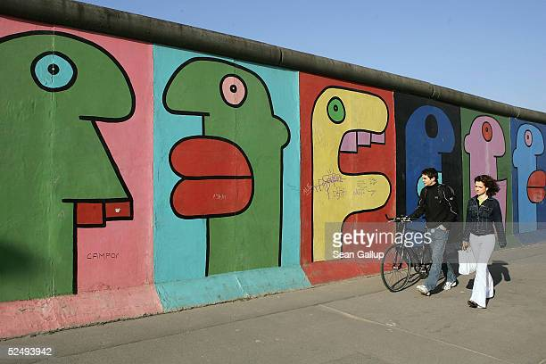 Couple pass by a still-standing section of the Berlin Wall, known as the East Side Gallery on March 30, 2005 in Berlin, Germany. According to a...