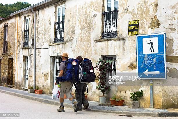 Couple pass sign on Camino de Santiago Pilgrim's Way to Santiago de Compostela at Triacastela in Galicia Spain
