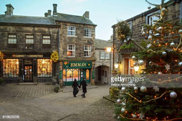 A Couple Passing Along Festive Cobbled Street With Christmas Tree
