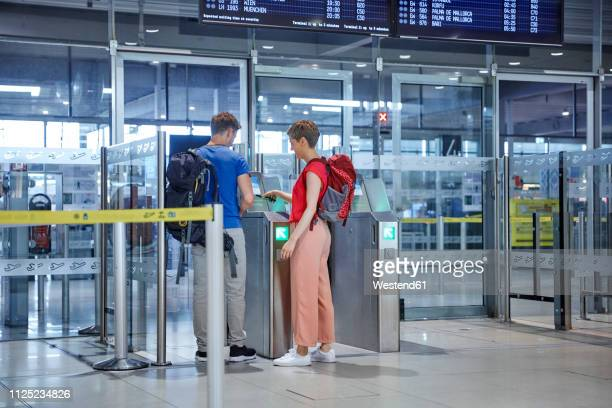 couple passing security gate at the airport - 税関 ストックフォトと画像