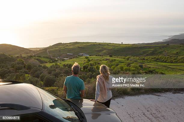 Couple pause at roadside, look upon sea, valley