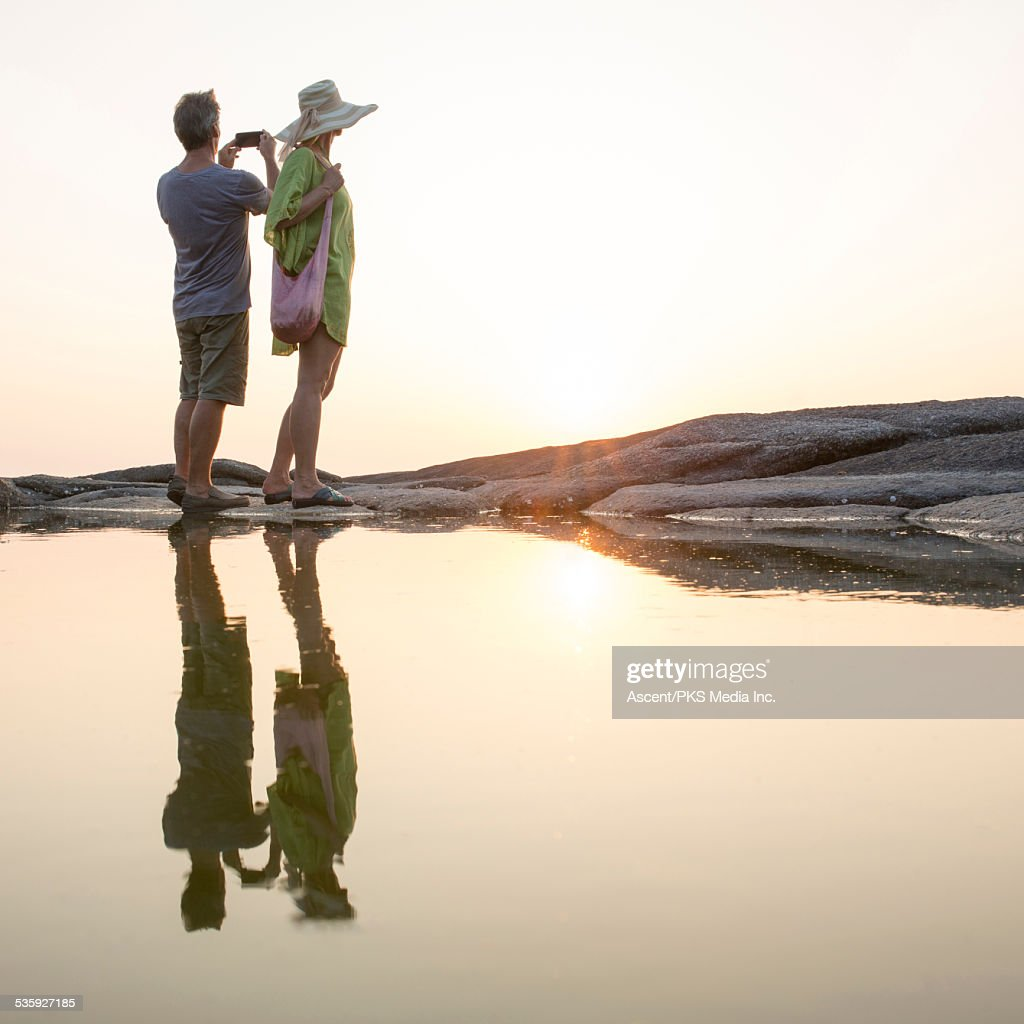 Couple pause besides pool,take pic of sun over sea : Stock Photo