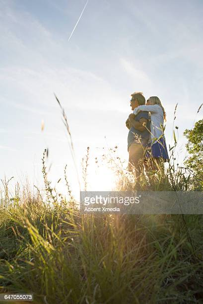Couple pause in green meadow,look out over sunrise