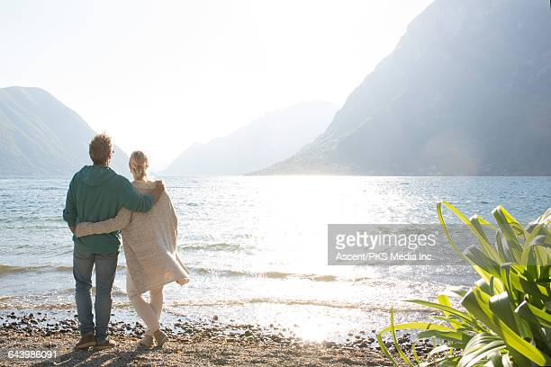 Couple pause on beach, look out to lake behind