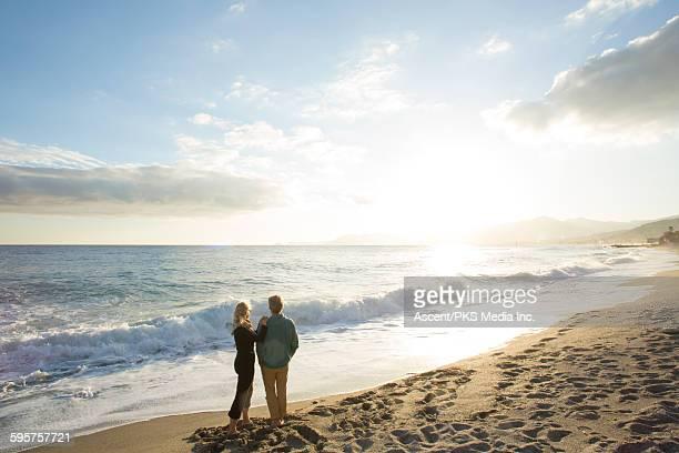 Couple pause on deserted beach, look towards sun