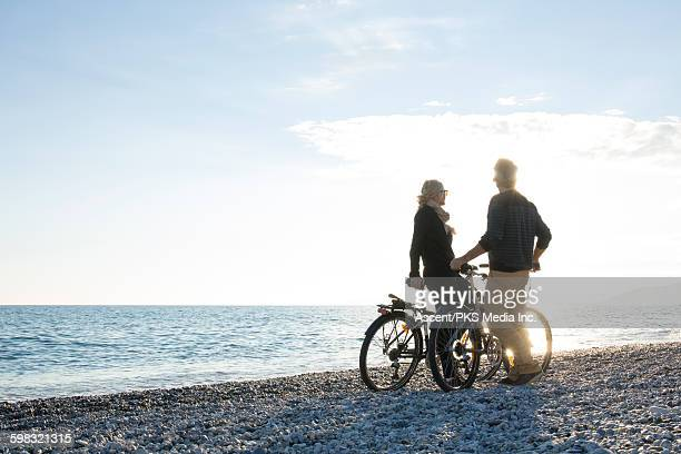 Couple pause with bikes on pebble beach, sunrise