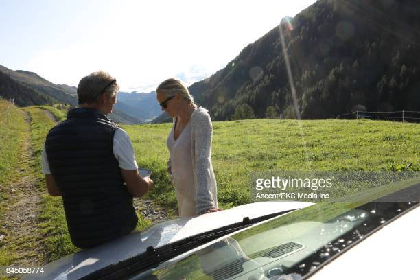 Couple pause with car on mountain track, consult digital tablet