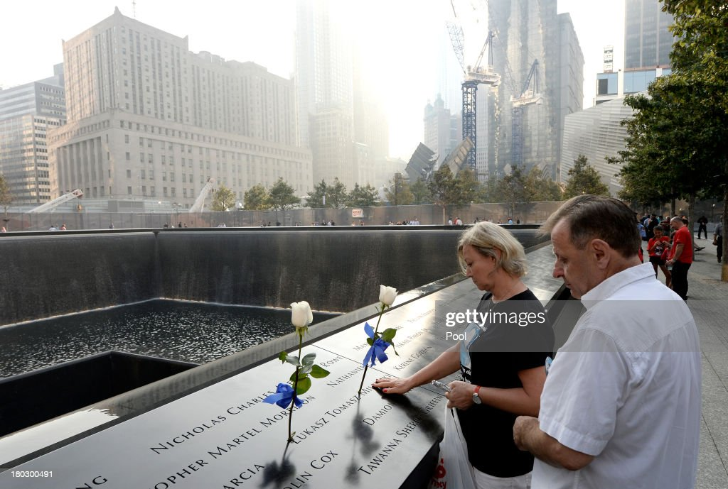 A couple pauses along the edge of the North Pool at the 9/11 Memorial during ceremonies for the twelfth anniversary of the terrorist attacks on lower Manhattan at the World Trade Center site on September 11, 2013 in New York City. The nation is commemorating the anniversary of the 2001 attacks which resulted in the deaths of nearly 3,000 people after two hijacked planes crashed into the World Trade Center, one into the Pentagon in Arlington, Virginia and one crash landed in Shanksville, Pennsylvania. Following the attacks in New York, the former location of the Twin Towers has been turned into the National September 11 Memorial & Museum.