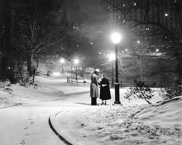 A couple pauses for a cigarette in snowy Central Park.