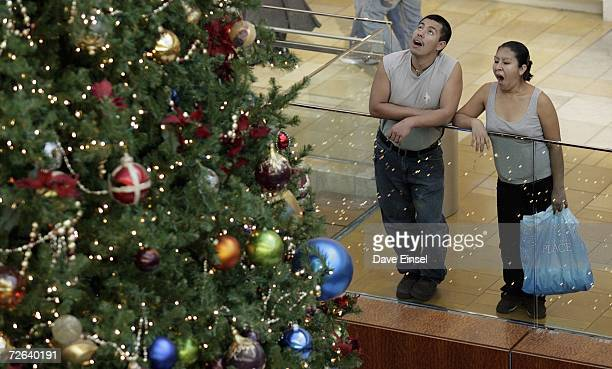 A couple pauses from shopping to look at a three story Christmas tree in the Galleria November 24 2006 in Houston Texas Shoppers hit stores all...