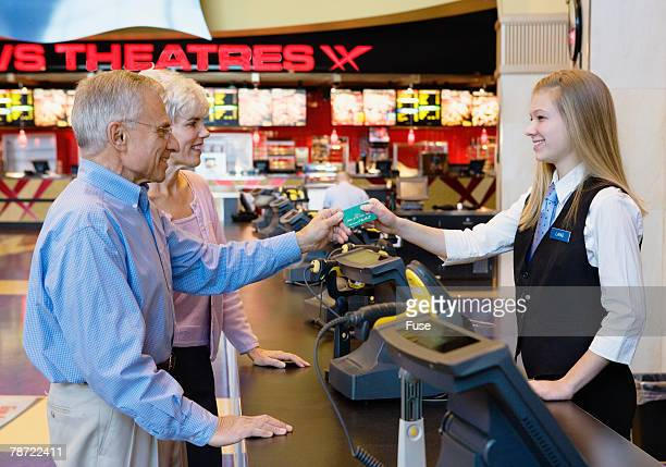 Couple Paying at Ticket Counter in Movie Theater