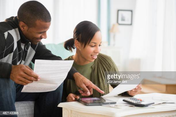 Couple paying bills in living room
