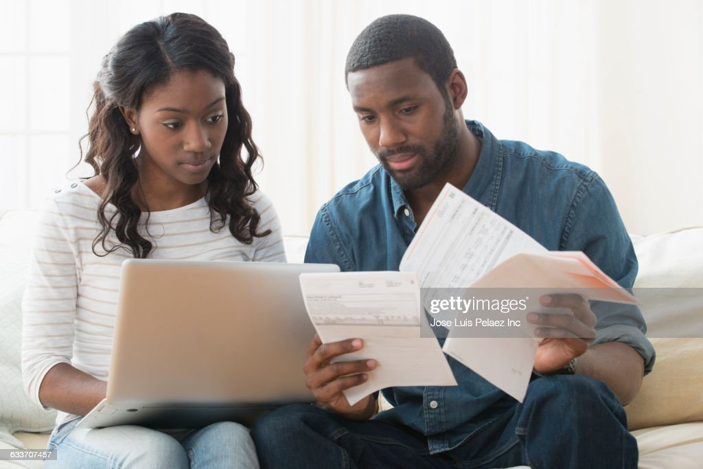 Couple paying bills on laptop : Stock Photo