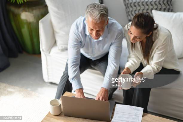 couple paying bills online at home - finance and economy stock pictures, royalty-free photos & images