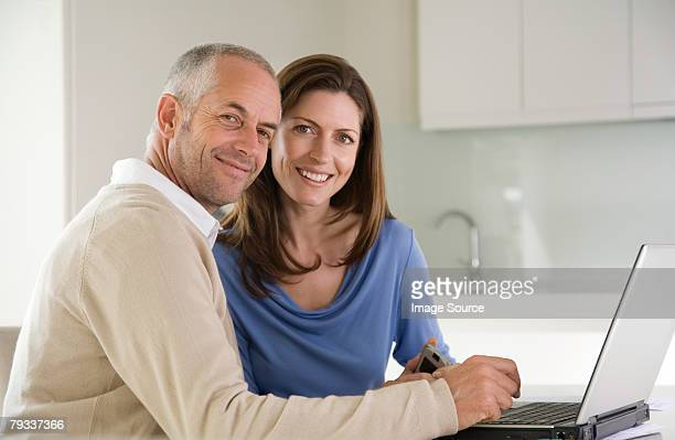 a couple paying bills online - 30 39 years stock pictures, royalty-free photos & images