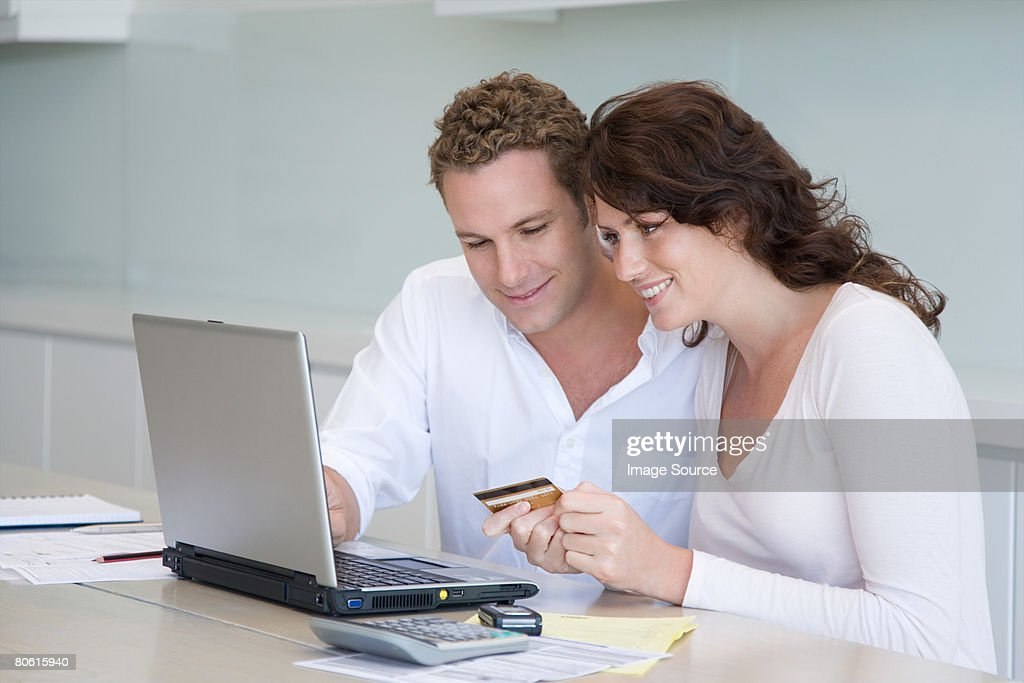 A couple paying bills online : Stock Photo