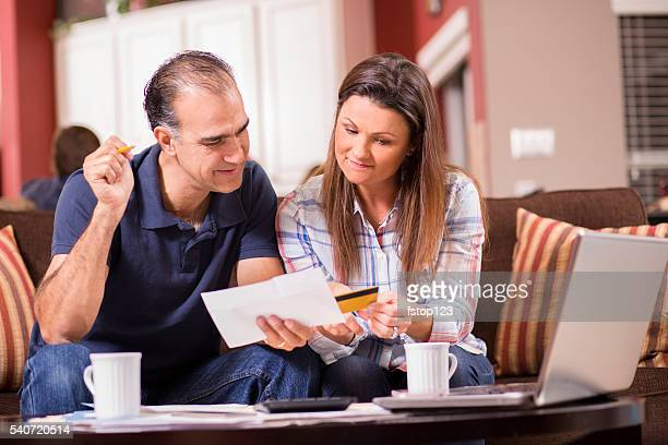 Couple paying monthly bills at home.  Credit card, laptop.