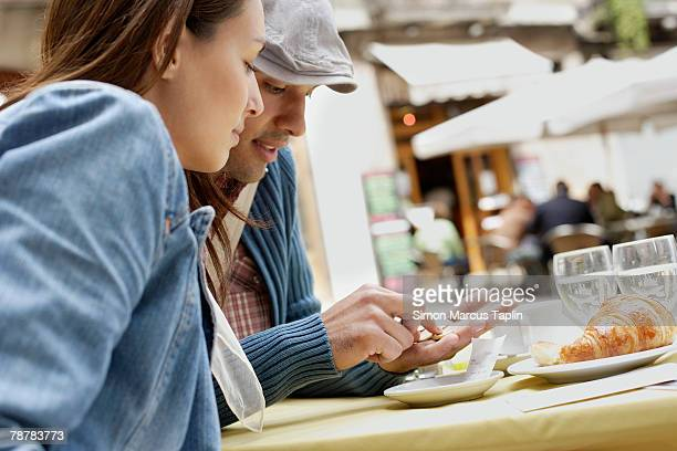 Couple Paying the Bill at Sidewalk Cafe